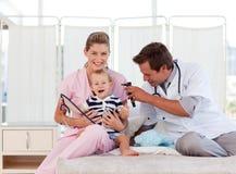 Doktoren, die um einem jungen Kind sich kümmern Lizenzfreie Stockbilder