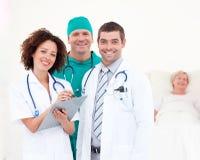 Doktoren, die um einen Patienten sich kümmern Stockfoto