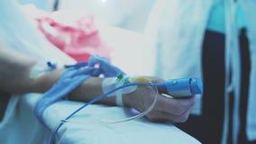 Doktoren im Krankenhaus, welches die Schutzkleidung durchführt Chirurgie unter Verwendung der Ausrüstung trägt stock footage
