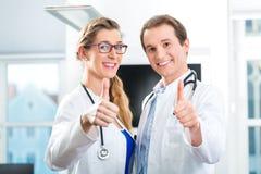 Doktoren - Mann und Frau, stehend mit einem Stethoskop Stockfoto