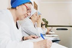 Doktoren am Tisch Lizenzfreie Stockfotos