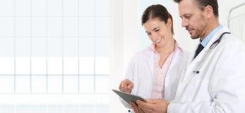 Doktorer använder den digitala minnestavlan, begrepp av medicinskt konsultera royaltyfri bild