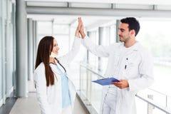 Doktorer höga fem efter lyckad kirurgi royaltyfri bild