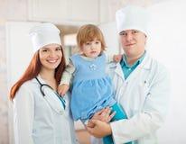 Doktorer med behandla som ett barn flickan i kliniken Arkivbild