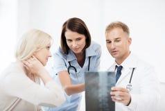 Doktorer med patienten som ser röntgenstrålen arkivfoto