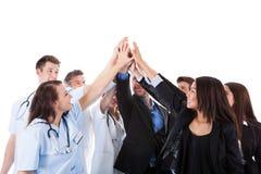 Doktorer och chefer som gör gest för höjdpunkt fem Fotografering för Bildbyråer