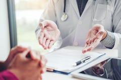 Doktorer och patienter sitter och talar På tabellen nära fönstret arkivbild