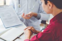 Doktorer och patienter sitter och talar På tabellen nära fönstret arkivfoto
