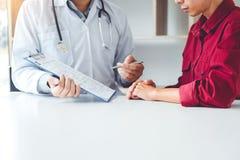 Doktorer och patienter sitter och talar På tabellen nära fönstret arkivfoton