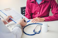Doktorer och patienter sitter och talar P? tabellen n?ra f?nstret i sjukhuset royaltyfria foton