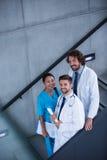 Doktorer och sjuksköterska som rymmer medicinska rapporter som står på trappa Arkivfoto