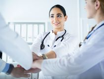 Doktorer och sjuksk?terskor i ett medicinskt lag som staplar h?nder arkivbilder