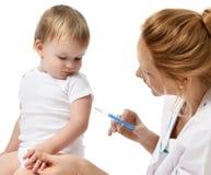 Doktorer räcker med injektionssprutan som vaccinerar barnet, behandla som ett barn influensainjektionskottet Arkivbilder