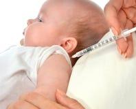 Doktorer räcker med injektionssprutan som vaccinerar barnet, behandla som ett barn influensa Fotografering för Bildbyråer
