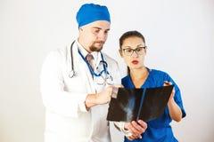 Doktorer ser röntgenstrålen, ser diskuterar de problemet och det Vit bakgrund royaltyfri foto