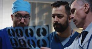 Doktorer som analyserar MRI-bildl?sningsresultat arkivfoto