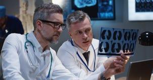Doktorer som analyserar MRI-bildl?sningsresultat arkivbild