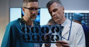 Doktorer som analyserar MRI-bildl?sningsresultat arkivbilder