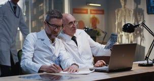 Doktorer som analyserar MRI-bildl?sningsresultat royaltyfri fotografi