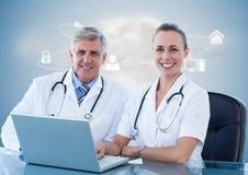 Doktorer som använder bärbara datorn på skrivbordet mot digitalt frambragd bakgrund royaltyfri bild