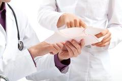 Doktorer som diskuterar en läkarundersökning, resulterar Royaltyfri Bild