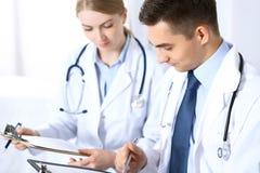 Doktorer som diskuterar läkarbehandlingrekord, bildar eller studerar på den medicinska konferensen Sjukvård, försäkring och medic royaltyfria foton