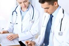 Doktorer som diskuterar läkarbehandlingrekord, bildar eller studerar på den medicinska konferensen Sjukvård, försäkring och medic arkivfoto
