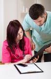Doktorer som gör läkarundersökninganmärkningar Fotografering för Bildbyråer