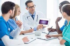 Doktorer som har konversation och ser minnestavlan arkivbilder