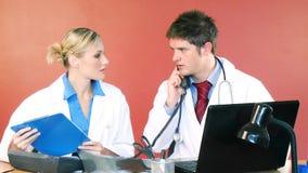 Doktorer som i regeringsställning arbetar och talar på telefonen arkivfilmer