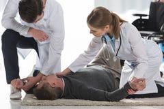 doktorer som kontrollerar puls av royaltyfria foton