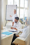 Doktorer som lyssnar till instruktören i medicinskt seminarium royaltyfri fotografi