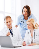 Doktorer som ser bärbara datorn på möte arkivfoton