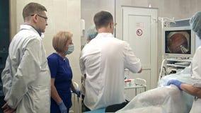 Doktorer som ser endoscopen, övervakar under kirurgisk operation arkivfilmer
