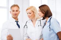 Doktorer som ser minnestavlaPC arkivbild