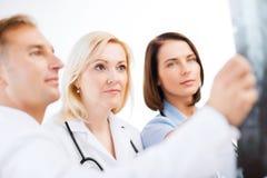 Doktorer som ser röntgenstrålen royaltyfria foton