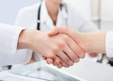 Doktorer som skakar händer på skrivbordet Arkivbilder