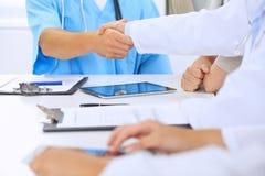 Doktorer som till varandra skakar fulländande övre medicinskt möte för händer Arkivfoto