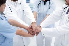 Doktorer som tillsammans rymmer händer på sjukhuset Royaltyfria Foton