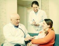 Doktorer som undersöker behandla som ett barn lite, i armar av den lyckliga modern Royaltyfria Foton