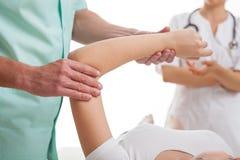 Doktorer som undersöker den sårade armen fotografering för bildbyråer