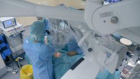 Doktorer som utför en kirurgi genom att använda den medicinska roboten Innovativt medicinbegrepp arkivfilmer