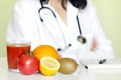 Doktorernährungswissenschaftler im Büro mit gesunden Früchten Stockbilder