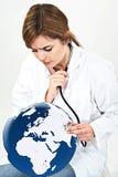 Doktorfrau überprüfen Weltkugel mit ihrem Stethoskop lokalisierten O Lizenzfreies Stockbild