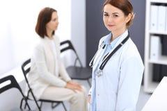 Doktorfrau bei der Arbeit Porträt des netten Lächelns des weiblichen Arztes bei der Stellung des nahen Aufnahmeschreibtisches an  stockfoto