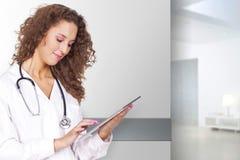 Doktorfrau, die einen tragbaren Computer hält stockfotos