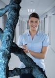 Doktorfrau, die mit DNA-Strang 3D steht Lizenzfreies Stockfoto