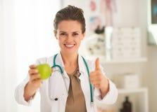 Doktorfrau, die sich Apfel und Daumen zeigt Stockfoto