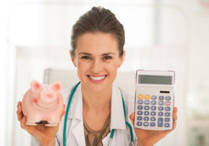 Doktorfrau, die Sparschwein und Taschenrechner zeigt Lizenzfreies Stockbild