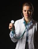 Doktorfrau, die Stethoskop auf schwarzem Hintergrund verwendet Stockbilder